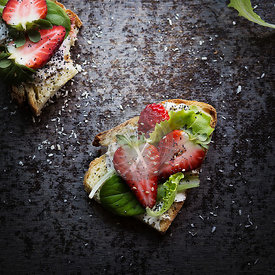 Slices of bread with cheese, salad and strawberries