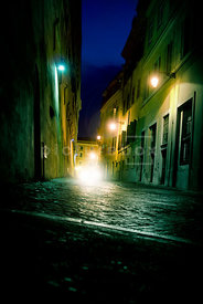 An atmospheric image of a cars headlights coming down an italian street at night.