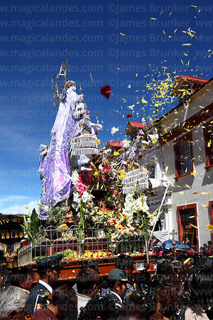 Devotees throw flower petals over Virgen de la Candelaria during main procession for festival, Puno, Peru