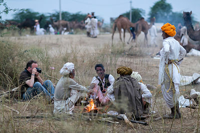 A veteran photojournalist (left) shows the right way to photograph in India, sitting on the ground, interacting with the peop...