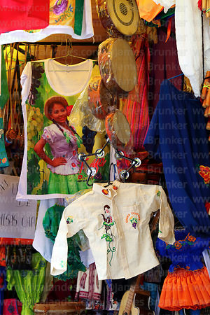 Embroidered man's shirt (camisa chapacha) and percussion instruments hanging outside souvenir shop, Tarija, Bolivia