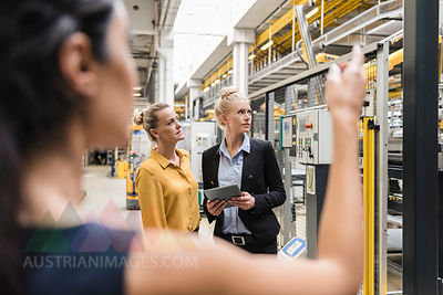 Women with tablet talking in modern factory