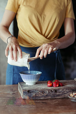 Woman preparing muesli, pouring yogurt in bowl, fresh strawberries