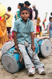 A boy plays drums during Chhath Puja, Varanasi, India. Chhath Puja is a devotion to the Sun God Surya in which people gather ...