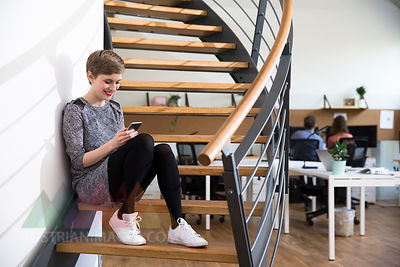 Smiling woman sitting on stairs in modern office looking at cell phone