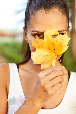 Woman holding up an autumn leaf in front of her face