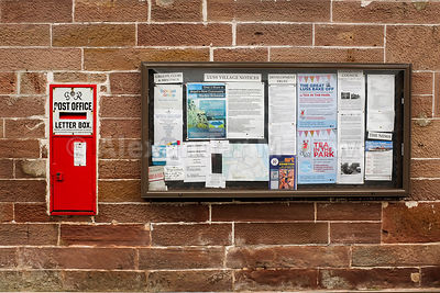 Vintage wall mounted  George VI letter box alongside the Luss village noticeboard