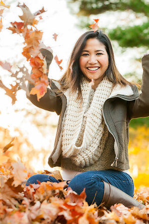 Young Asian woman playing in leaf pile