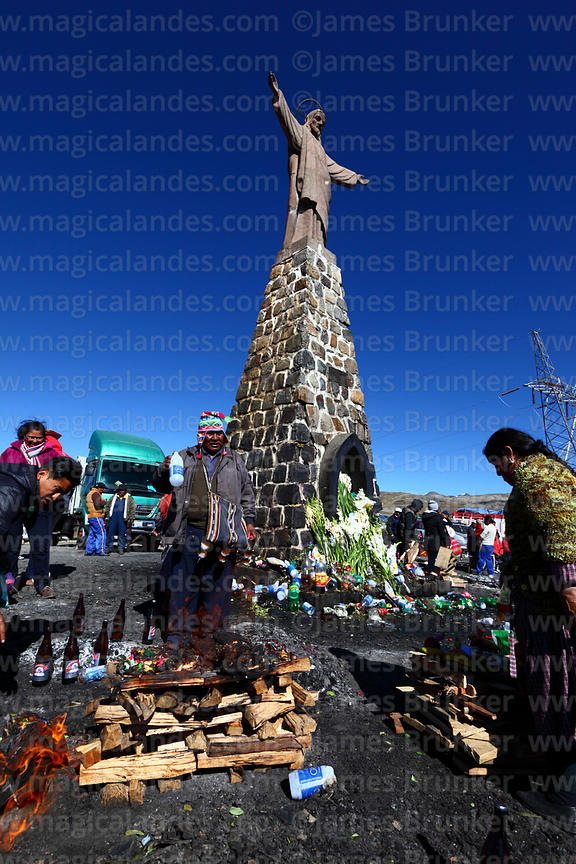 Aymara shaman or yatiri blessing offerings (called k'oas) to Pachamama with alcohol below Christ statue, La Cumbre, Cordiller...