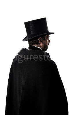 A Victorian man in a hat and cloak, in semi-silhouette – shot from eye level.