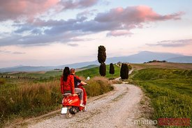 Couple riding an italian vespa motorcycle in Tuscany