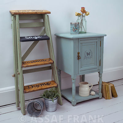 Old fashioned cabinet with flower vase and a ladder