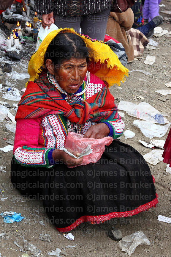 Quechua woman collecting melted wax from candles left by devotees during Qoyllur Riti festival, Peru