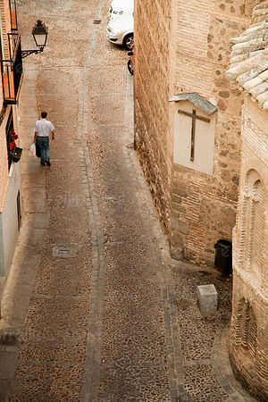 A man walks down a narrow cobblestone street in an old Spanish city.