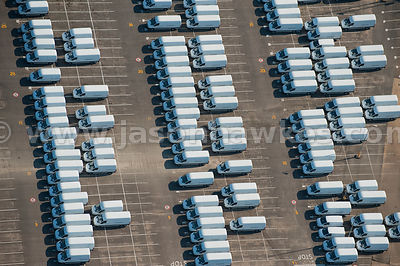 Aerial view of cars and vans at shipping dock yard