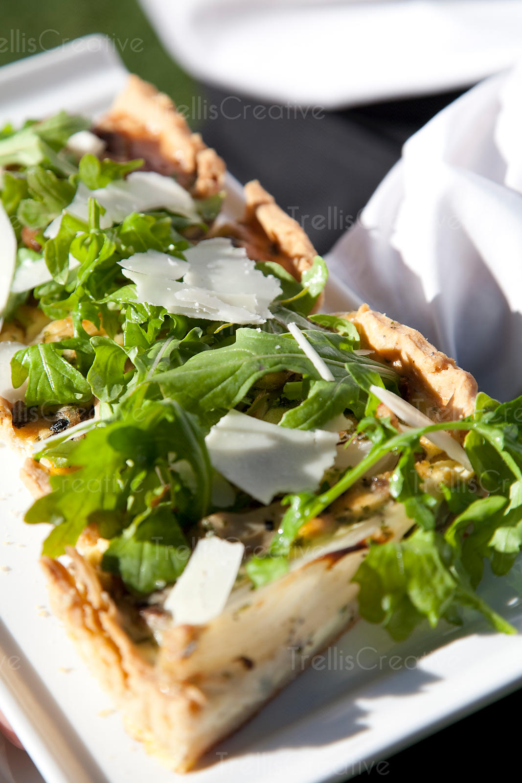 Potato and bacon tarte appetizer with arugula and shaved parmesan cheese