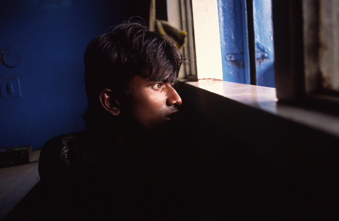 India - Delhi - A boy on the run from the police peers from a window, New Delhi