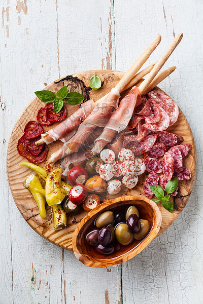 Cold meat plate with grissini bread sticks on blue wooden background