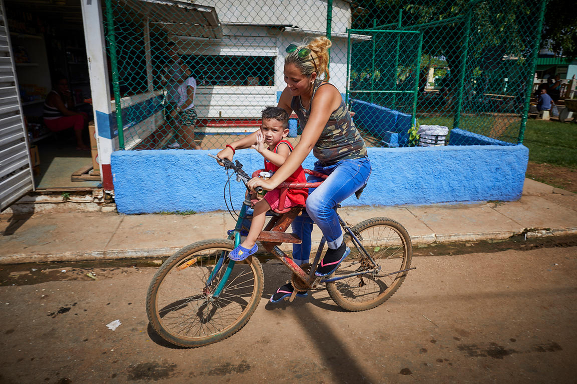 A mother and child riding a bike