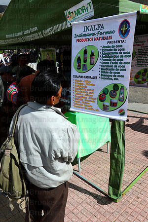 Man reading about coca based medicinal products at stall at trade fair promoting alternative products made from coca leaves ,...