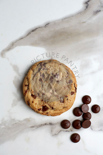 Single chocolate chip cookie on a white marble table