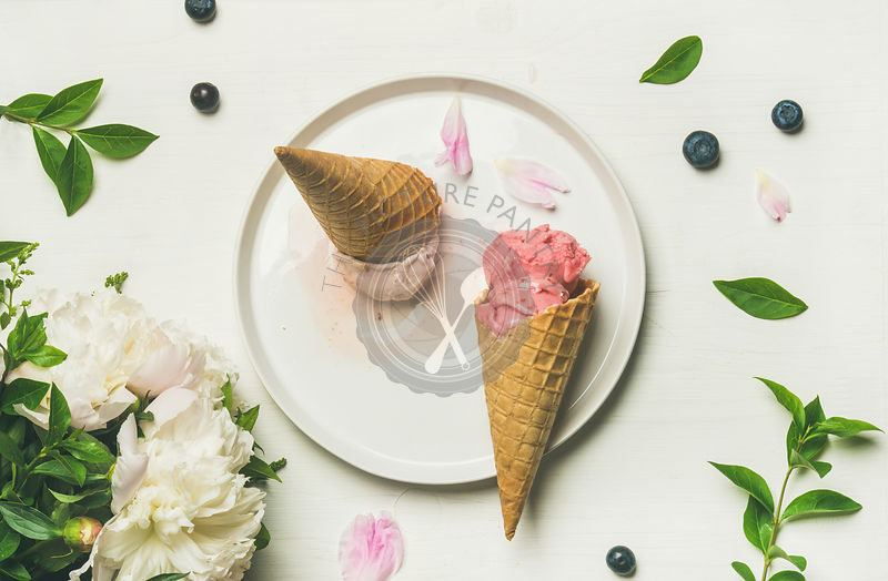 Flat-lay of pink strawberry and coconut ice cream scoops, sweet cones and peony flowers bouquet
