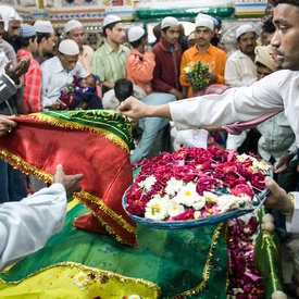 Worshippers (both Hindu and Muslim) pray and make offerings over the tomb of Hazrat Nizamuddin Awlia, a sufi saint who died i...