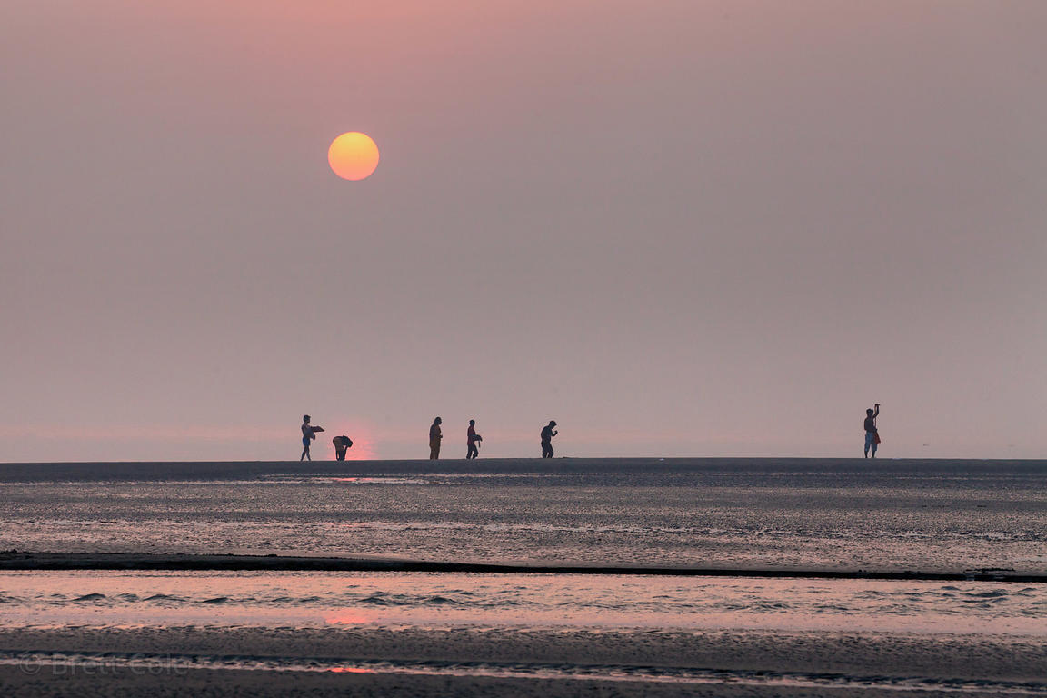 Pilgrims walk on the beach at sunset during the Gangasagar Mela, Sagar Island, India.