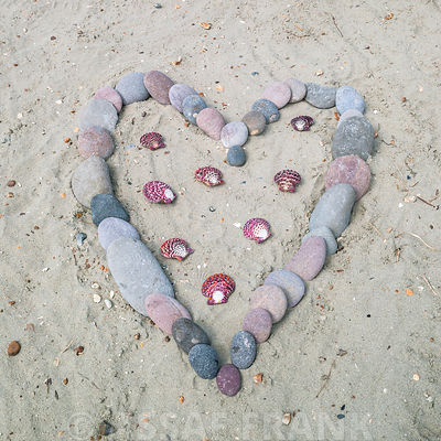 Heart shape made of pebbles and sea shells on the beach