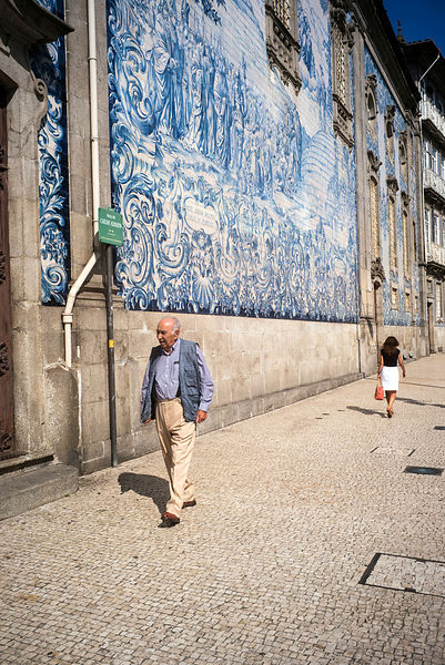 An elderly man walks past the Capela Das Almas in Porto, Portugal