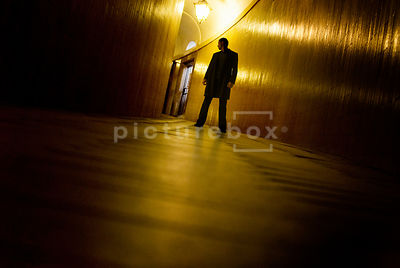 An atmospheric image of a lone mystery man looking over his sholder in the dimly lit corridor of an old building.