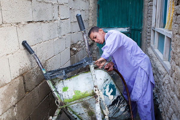Bashir, 13 ans, utilise l'eau du puit pour nettoyer sa brouette, Kaboul, Afghanistan / Bashir, 13, uses well water to clean h...