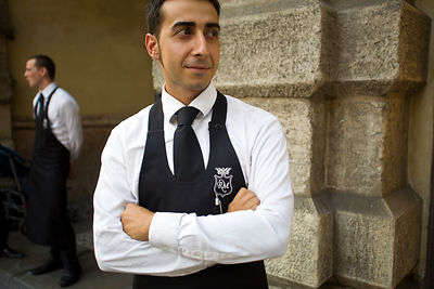 Italy - Verona - A waiter from a restaurant waits on the street