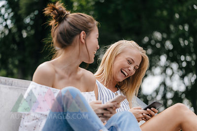 Two laughing young women with cell phones outdoors