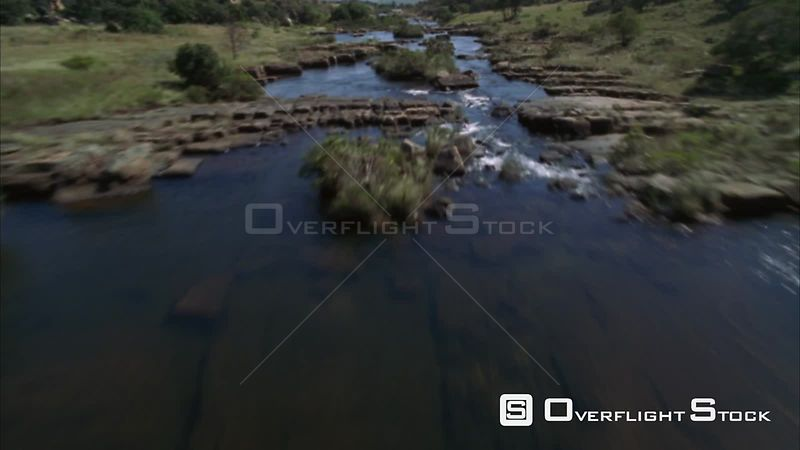 Aerial shot over a rocky river then over the edge of a cliff to a river canyon Sabie. Mpumalanga South Africa