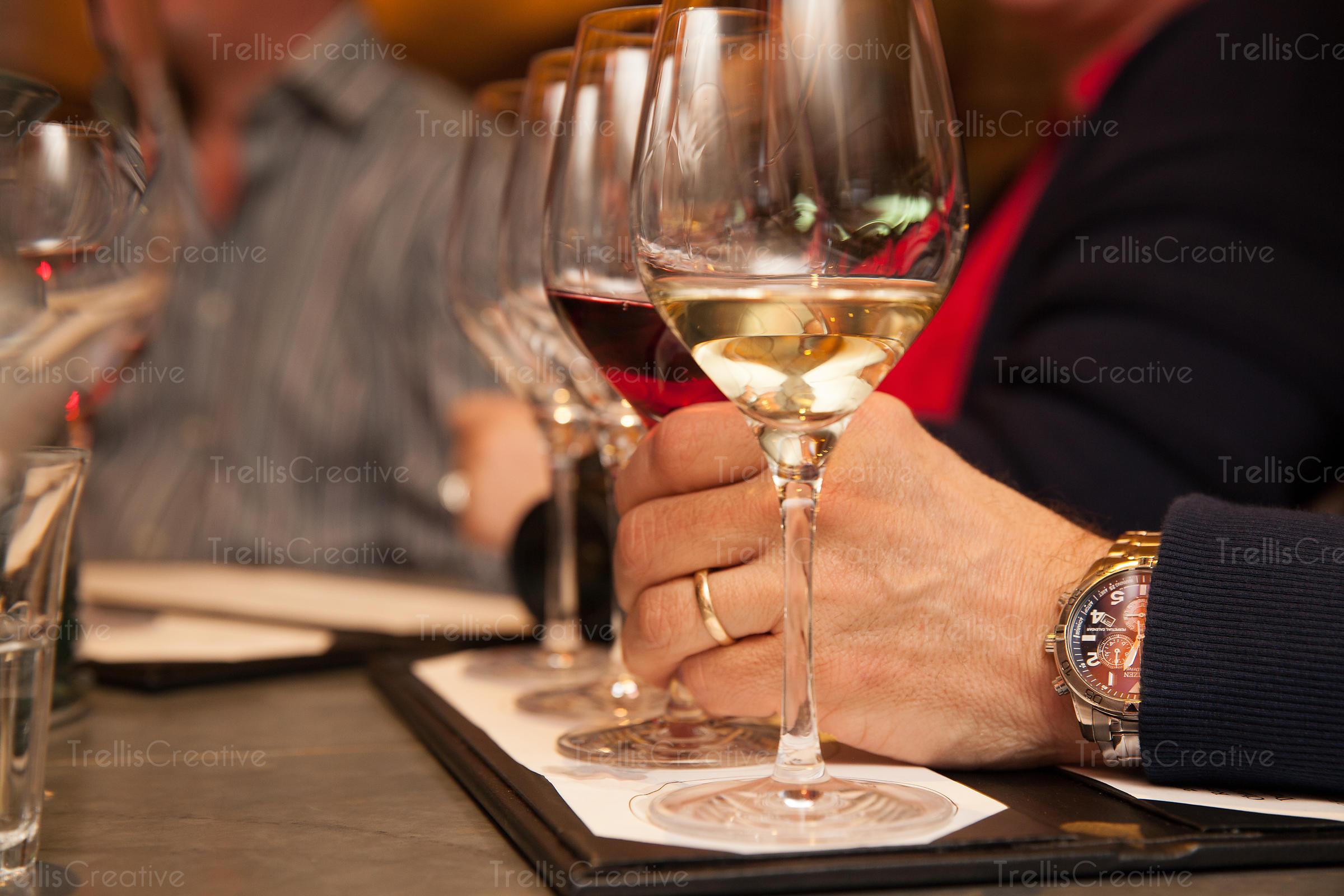 Close-up of a man's hand holding a wine glass ata tasting
