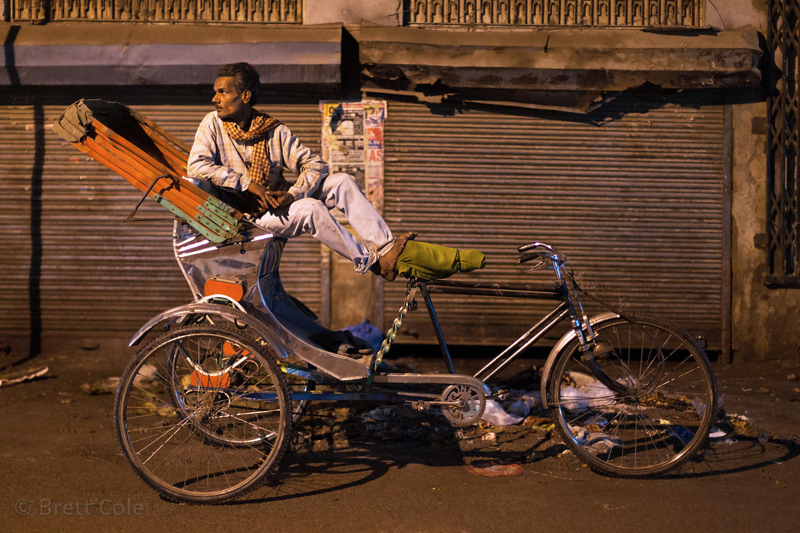 Cycle rickshaw driver at night in Varanasi, India.