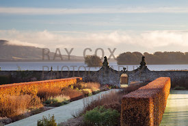 Last moments of saturated winter sun on the beech hedges and double herbaceous borders flanking the central path; Loch Leven ...