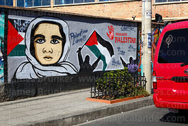 Minibus with figure of Virgin Mary and rosary on rear window driving past mural showing support for Palestine, La Paz, Bolivia