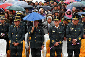 Army officer holding broken umbrella during central mass for the Virgen de la Candelaria festival, Puno, Peru