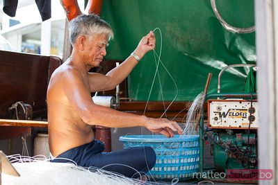 Old chinese fisherman working on his boat, Hong Kong
