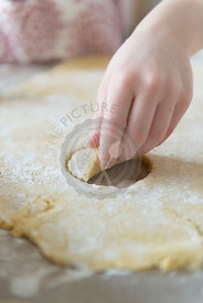 A child baking cakes. Cutting shapes out of pastry.