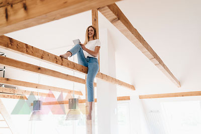 Carefree young woman sitting on ceiling joist