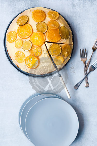 Homemade orange cake iced and decorated with slices of candied lemon, lime and orange beside three plates and forks.