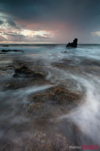 Lonely rock in stormy sea at sunrise