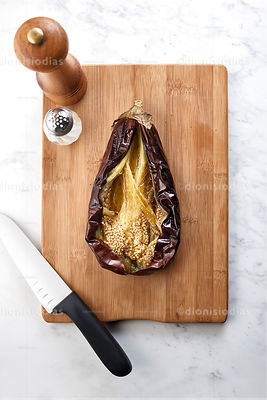 Roasted eggplant and open on cutting board with Salter and pepper grinder Knife