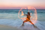 Traditional maya fire dancer at sunset on the beach.  Mexico