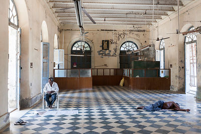 A building worker asleep on a break inside the derelict Hotel du Ville that has been saved by INTACH (Indian National Trust f...