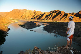 One man standing on a cliff looking down onto a wide river in the desert, with mountains on the far bank, at sunset