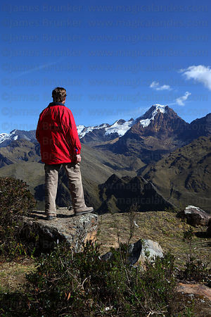Hiker looking at view towards Mt Akamani on Curva to Pelechuco trek , Cordillera Apolobamba , Bolivia